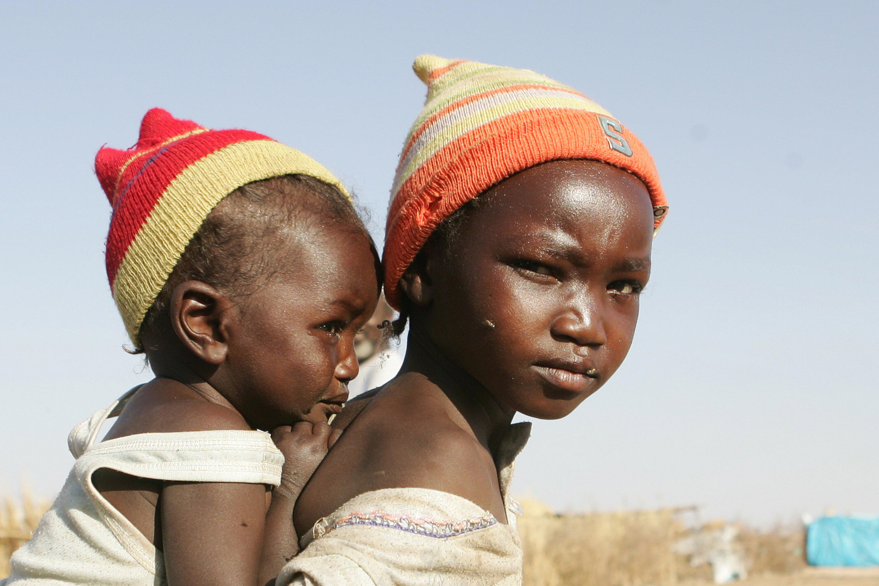 A displaced Sudanese girl carries her sister at the Otach Displaced Persons camp in the city of Nyala, in Sudan's strife-torn Darfur region, 22 February 2007.