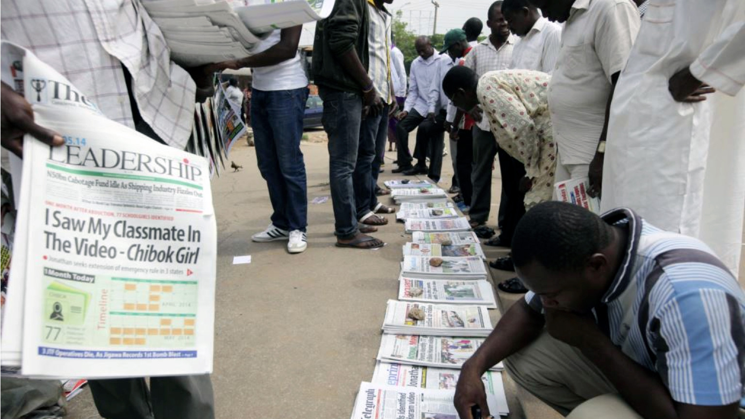 In some African countries, it's not unusual to see crowds reading newspapers that have been laid out on sidewalks.